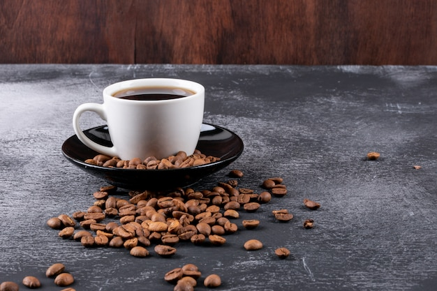 Coffee cup with coffee beans on dark table