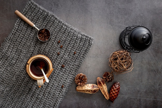 Coffee cup with coffee beans on a grey knitted scarf