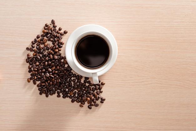 木製の表面にコーヒー豆とコーヒーカップ