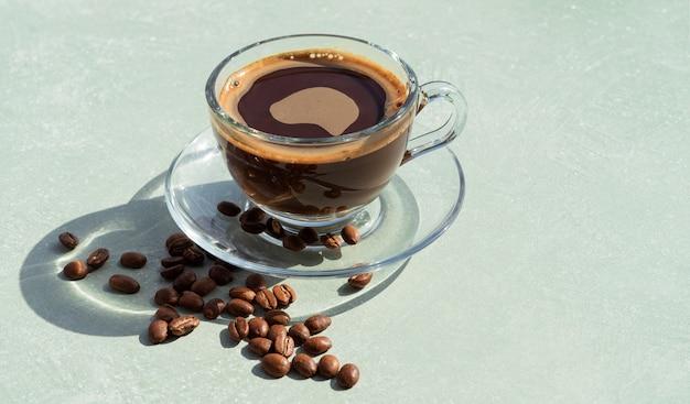 白い背景の上の外のコーヒー豆とコーヒーカップ。