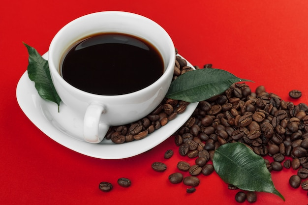 Coffee cup with coffee beans on red .