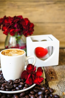 Coffee cup with coffee grains and flowers