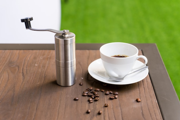 Coffee cup with coffee grinder on table