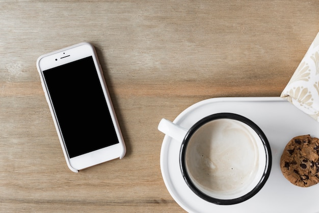 Coffee cup with cookie on white tray and smartphone on wooden backdrop