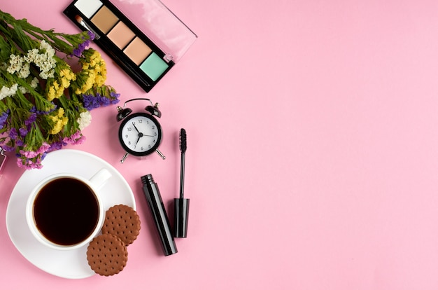 Coffee cup with cookies, alarm clock, flowers, mascara, on pink surface.