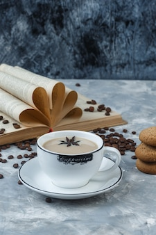 Coffee in a cup with cookies, coffee beans, book high angle view on a grungy plaster background