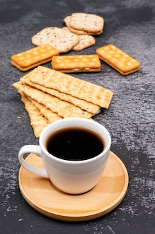 Coffee cup with cookies on dark table