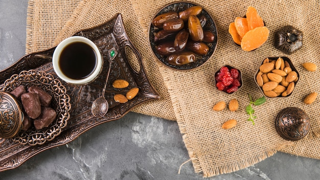 Coffee cup with dates fruit and almonds on metallic tray