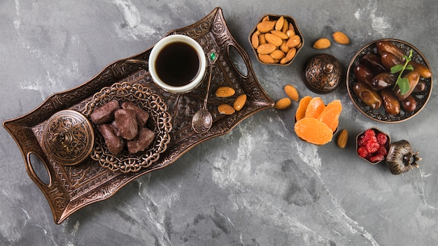 Coffee cup with dates fruit and almonds on tray