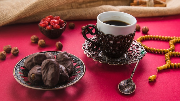 Coffee cup with dates fruit and beads on table