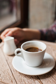Coffee cup with defocus woman hand holding milk pitcher in caf�