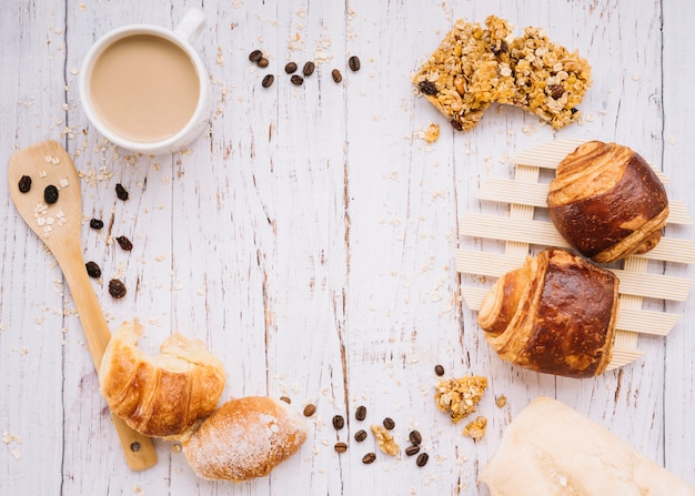 Coffee cup with different bakery on wooden table