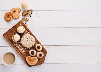 Coffee cup with different cookies on wooden board
