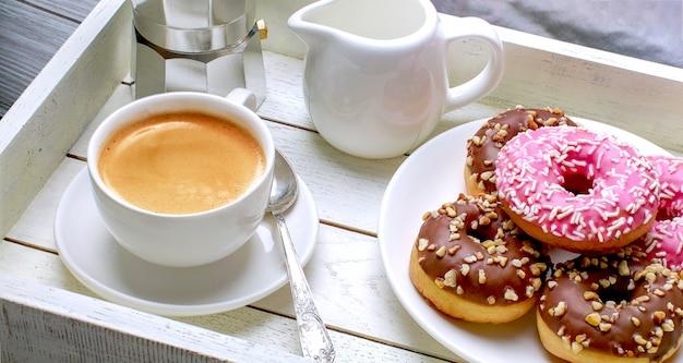Чашка кофе с пончиками на деревянном подносе Premium Фотографии