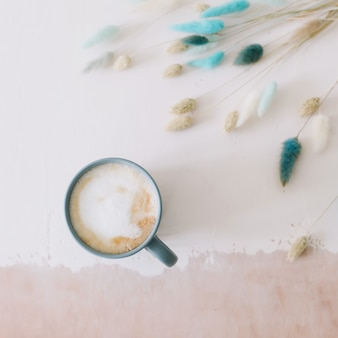 Coffee cup with dried flowers breakfast flatlay with big mug of milky cappuccino coffee and flowers rustic style good morning