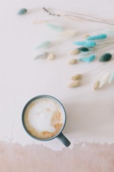 Чашка кофе с сушеными цветами сверху