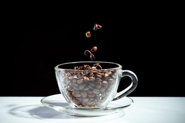 검은 배경에 떨어지는 콩과 커피 컵