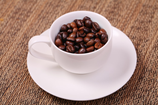 Coffee cup with fresh coffee beans on a brown background