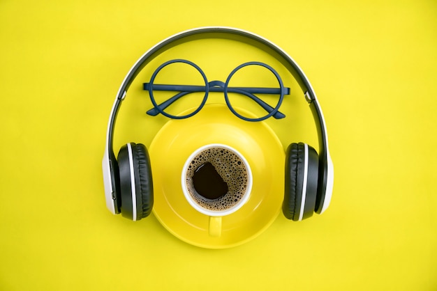 Coffee cup with headphone and teacher glasses on yellow paper background