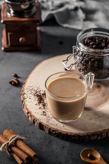 Чашка кофе с банкой и палочками корицы