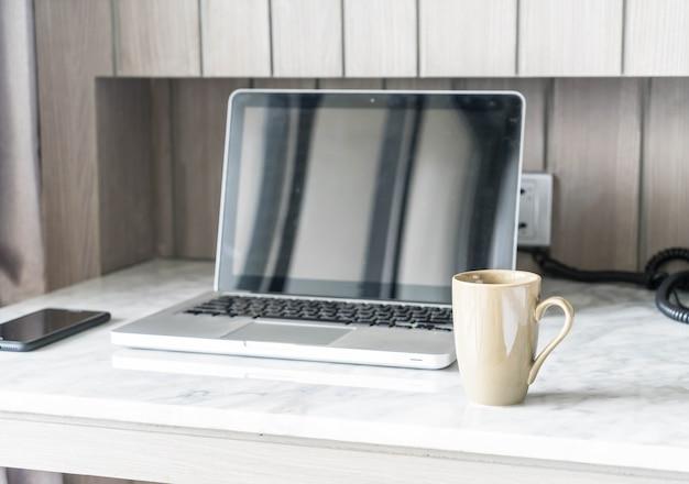 ラップトップと美しい豪華なテーブルの装飾のコーヒーカップ、リビングルームのインテリアの背景