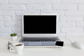 白い机の上にノートパソコンと携帯電話を持つコーヒーカップ
