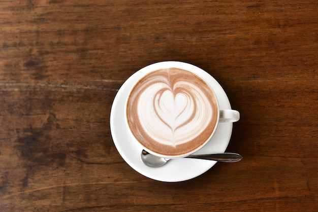 コーヒーブレークの時間に木製のテーブルメニューにラテアートのコーヒーカップ。ラテアートの泡のデザインパターンは、コーヒーを準備する方法です。