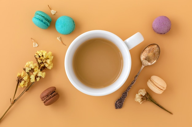 Coffee cup with macaroons, flower and vintage spoon, flat lay