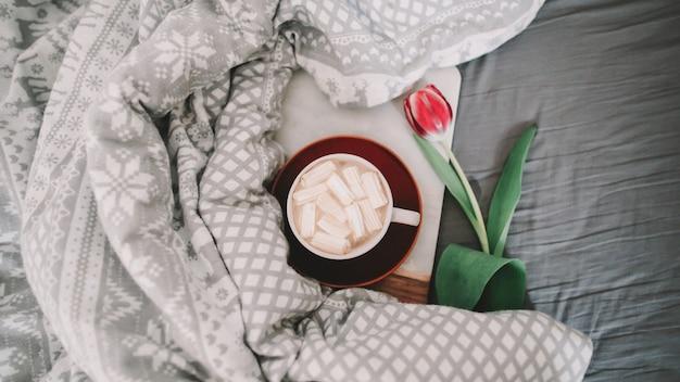 Чашка кофе с зефиром и красными тюльпанами в постели. концепция праздника, дня рождения, дня святого валентина, 8 марта