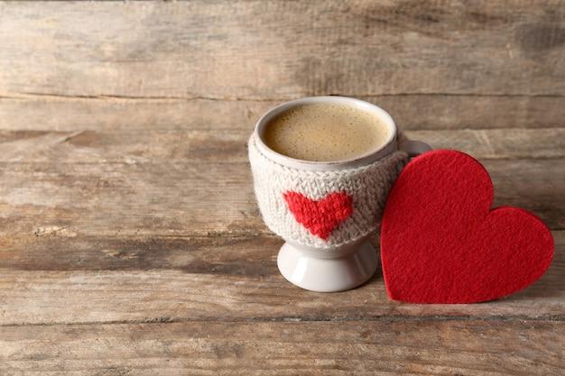 木製のテーブルのクローズアップにミルクとハートのコーヒーカップ