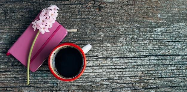오래 된 나무 기지에 노트북과 히 아 신 스 꽃과 커피 컵. 공간을 복사하십시오.