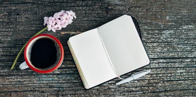 오래 된 나무 배경에 열려 노트북 및 분홍색 히 아 신 스 꽃 커피 컵. 공간을 복사하십시오.