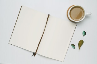 Coffee cup with open notebook on white wooden background