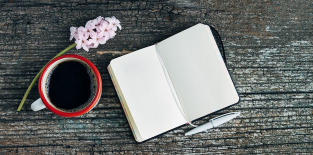 Coffee cup with open notebook and pink hyacinth flower on old wood background. copy space.