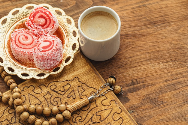 Coffee cup with oriental sweets on wooden table close up