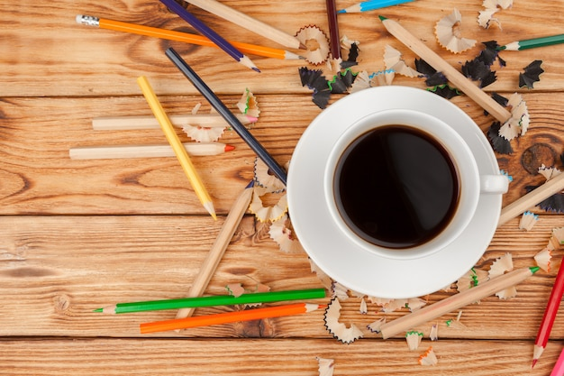 Coffee cup with pencils and pencil cuts on wooden background