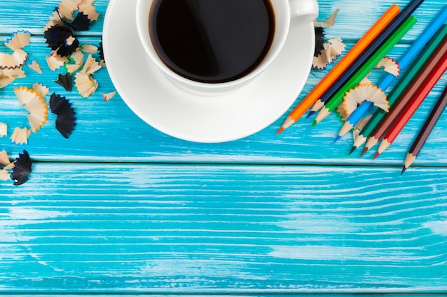 Coffee cup with pencils and pencil cuts on wooden