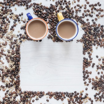 Coffee cup with raw and roasted coffee beans on wooden background