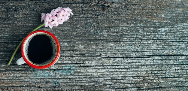 Coffee cup with red border and pink hyacinth flower on old wood background. copy space. top view.