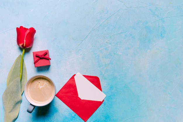 Coffee cup with red tulip on table