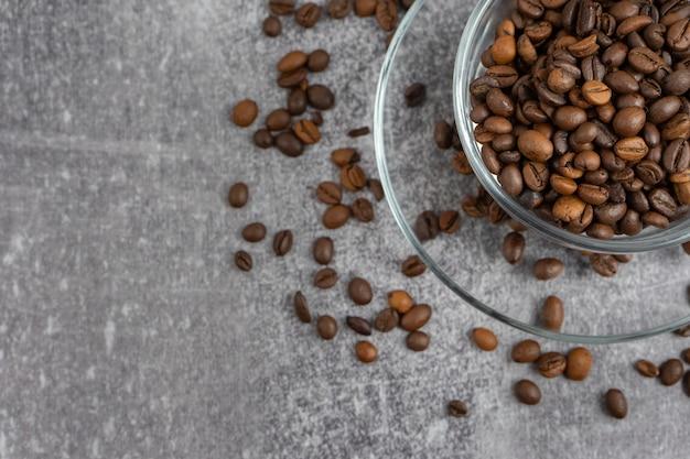 Чашка кофе с жареными бобами на сером фоне камня. вид сверху, плоская планировка с местом для текста