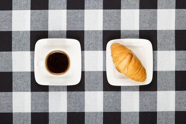 Coffee cup with saucer and croissant
