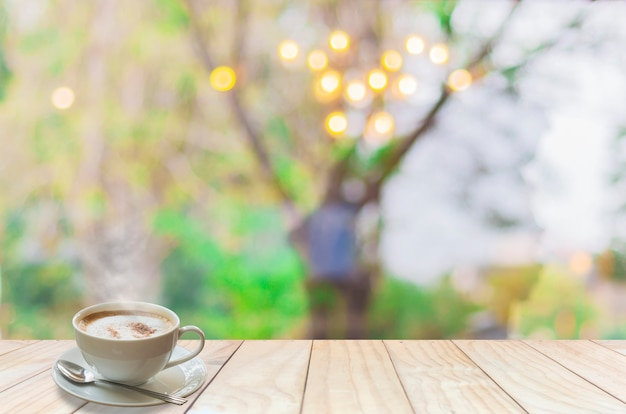 Coffee cup with smoke and spoon on white wooden terrace over blur light bokeh