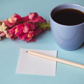 Чашка кофе с весенним цветком и нотами доброе утро на синем столе