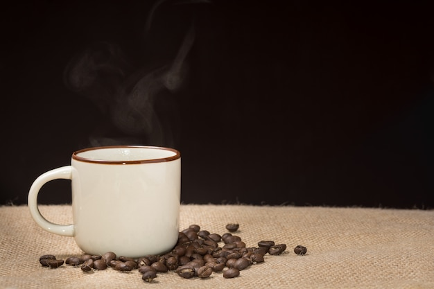 Coffee cup with steam and coffee beans on hemp sack