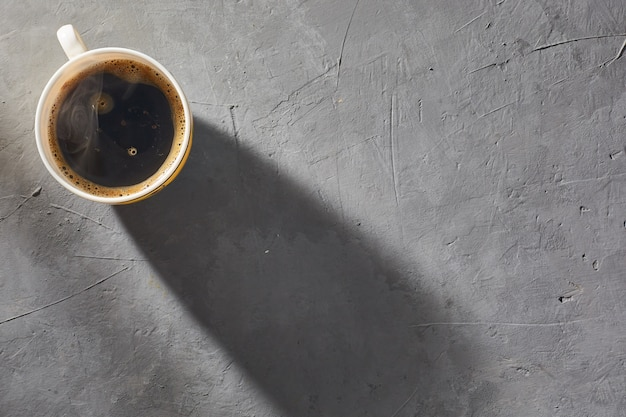Coffee cup with steam on a gray concrete background. top view. minimalism