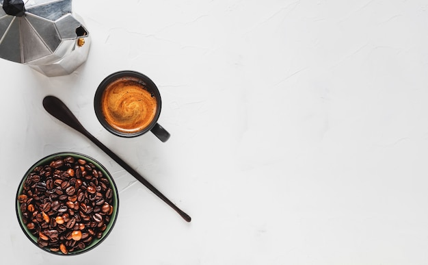 Coffee cup with strong espresso with foam, a coffee pot and coffee beans in a bowl on a white concrete surface