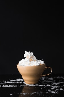 Coffee cup with whipped cream on black surface