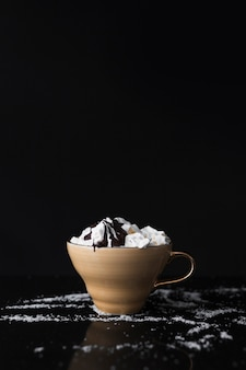 Coffee cup with whipped cream and chocolate syrup on black background