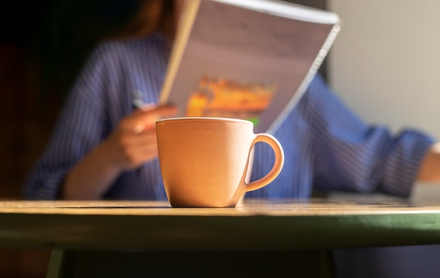 Coffee cup on wood table in cafe blurred female hands with texbook or notebook reading